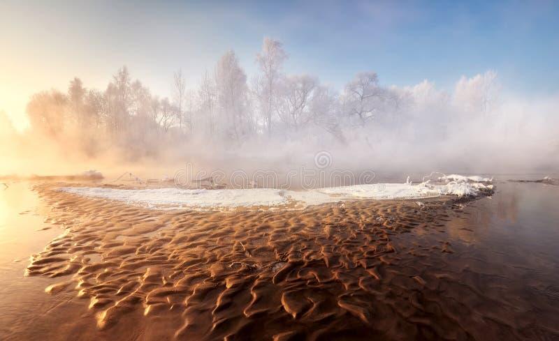 Eisige Landschaft des Wintermorgens mit einem kleinen Waldfluß und einer braunen sandigen Untiefe, ähnlich Lava lizenzfreies stockbild