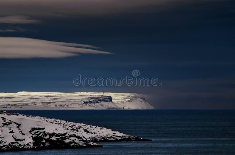 Eisige Nachtlandschaft der Nordpolarmeer Schwere kalte Naturnordklippen Dunkles tiefes blaues Wasser und Himmel, weiße Wolken stockfotos