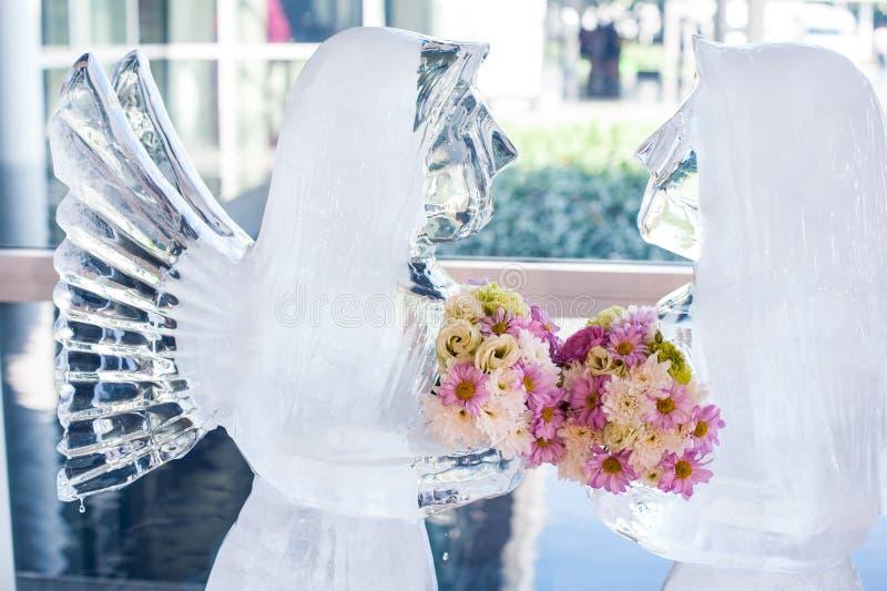 Eisige Skulptur des gefrorenen Engels mit schöner Blume für verziertes Heiratszeremoniegeschenk im Parteiraum lizenzfreie stockfotos