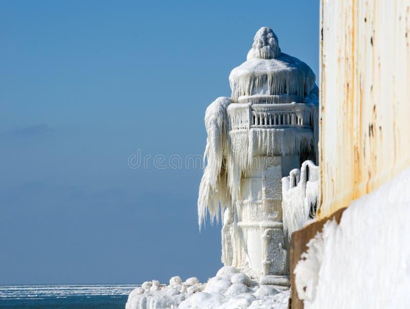 Eisiger Leuchtturm am Rand des kalten Wassers stockbilder