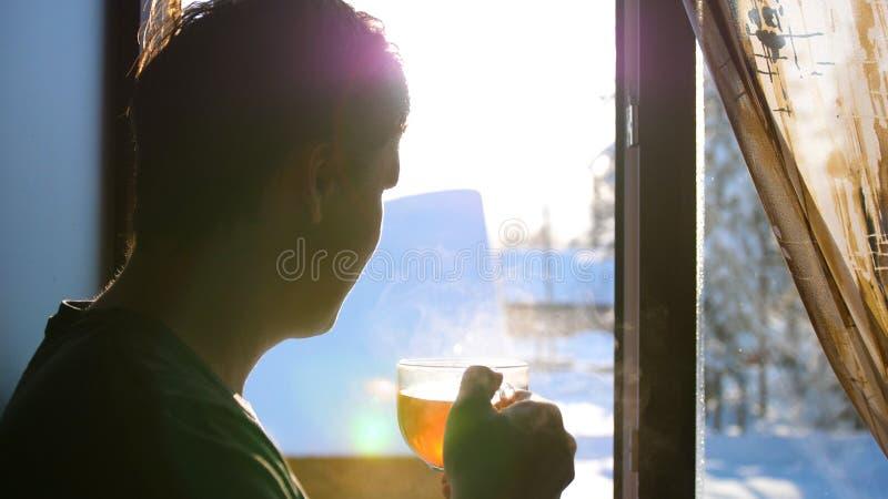Eisiger Tag des Winters Der Kerl früh morgens stehend am Fenster und am trinkenden heißen Tee lizenzfreies stockfoto