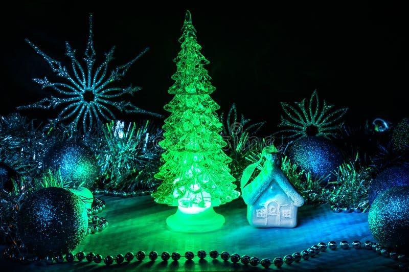 Eisiger Weihnachtsbaum, der mit rotem Licht auf einem blauen Hintergrund glüht lizenzfreie stockbilder