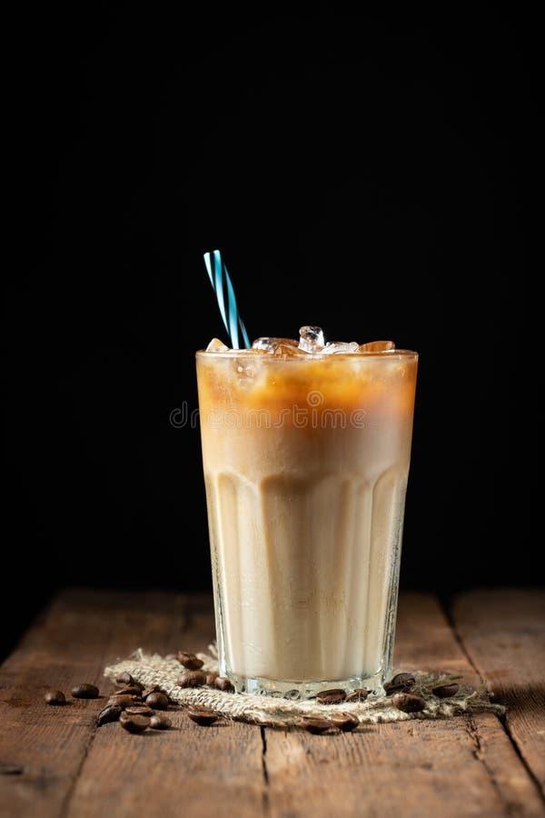Eiskaffee in einem hohen Glas lief mit Sahne vorbei und Kaffeebohnen auf einem alten rustikalen Holztisch aus Kaltes Sommergeträn stockfotos
