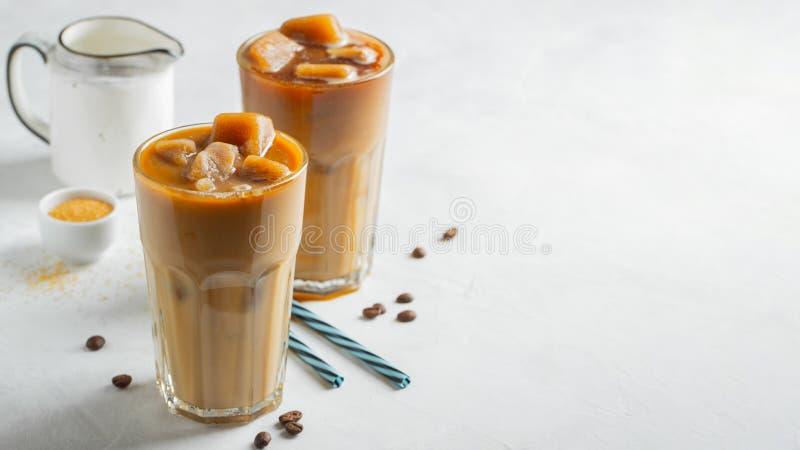 Eiskaffee in einem hohen Glas lief mit Sahne vorbei und Kaffeebohnen aus Kaltes Sommergetr?nk auf einem hellen Hintergrund Mit Ko lizenzfreies stockfoto