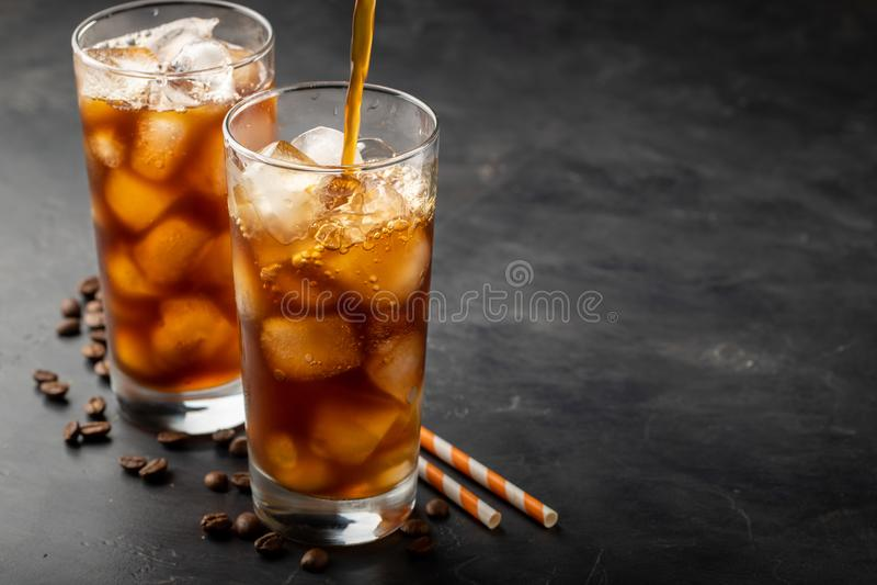 Eiskaffee in einem hohen Glas vorbei und in den Kaffeebohnen auf einem alten rustikalen Holztisch Kaltes Sommergetränk auf einem  stockfoto
