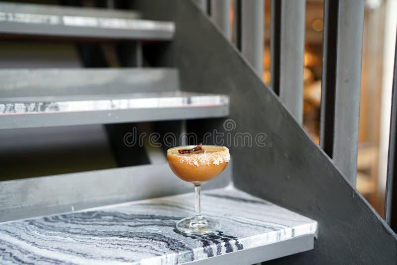 Eiskaffee mit frischem Saft - Ein salzgeradenes Espressoglas, gemischt mit handgearbeiteten Soda, Mango und Kalken, mit getrockne stockfotografie