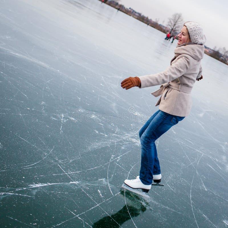 Eislauf der jungen Frau draußen auf einem Teich lizenzfreies stockbild