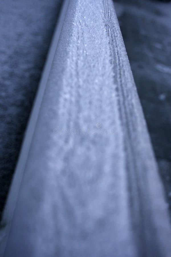 Eisspitzen auf einem hölzernen Handlauf stockbild