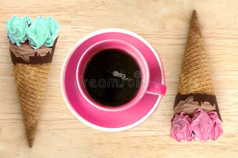 Eistüten und heiße Kaffeetasse auf hölzernem Weinlesehintergrund lizenzfreie stockfotografie