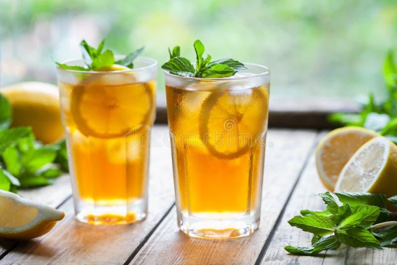 Eistee mit Zitronenscheiben und Minze auf Holztisch angesichts der Terrasse und der Bäume Schließen Sie herauf Sommergetränk lizenzfreie stockfotos