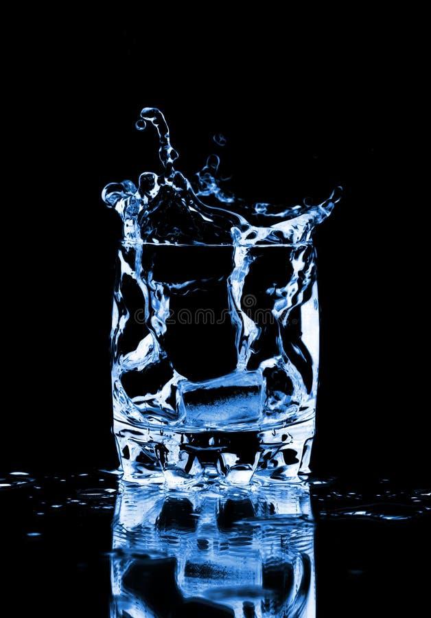 Eiswürfel, der in Glas Wasser spritzt stockfoto