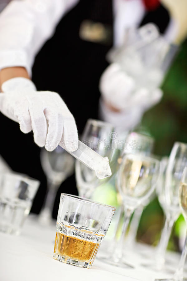 Eiswürfel, der weg im Weinbrandglas droping ist stockbilder