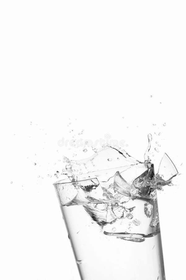 Eiswürfelspritzen auf Wasser gebrochenem Glas stockbild