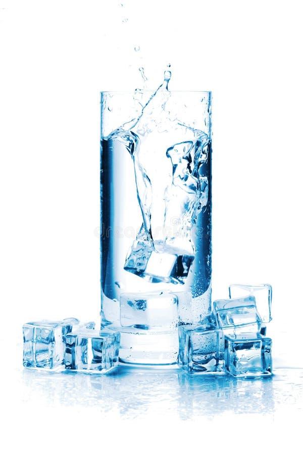 Eiswürfelspritzen in einem Glas Wasser stockbilder