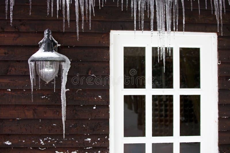 Eiszapfen auf dem Äußeren eines getäfelten hölzernen Hauses lizenzfreie stockbilder