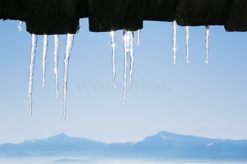Eiszapfen auf dem Dach eines Gebirgshauses lizenzfreie stockfotografie