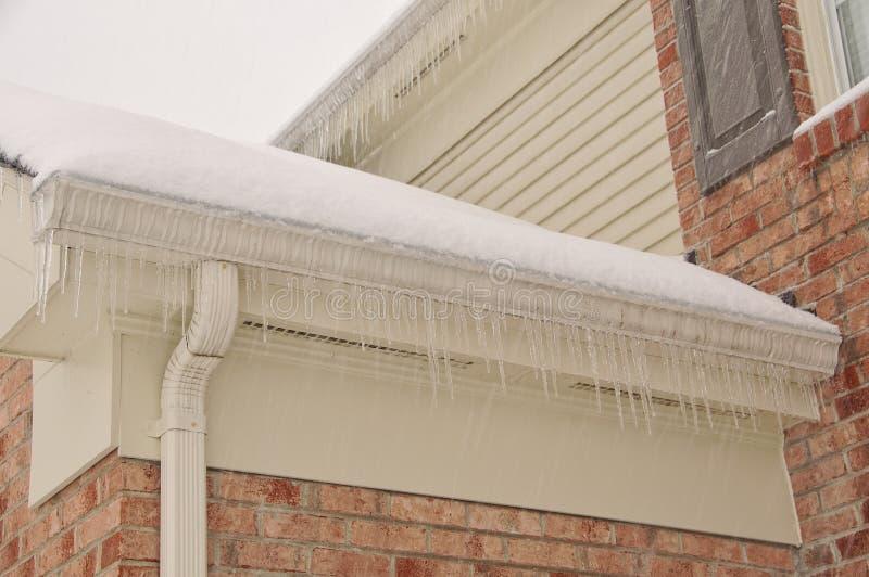 Eiszapfen auf den Dach-Gossen stockfotos