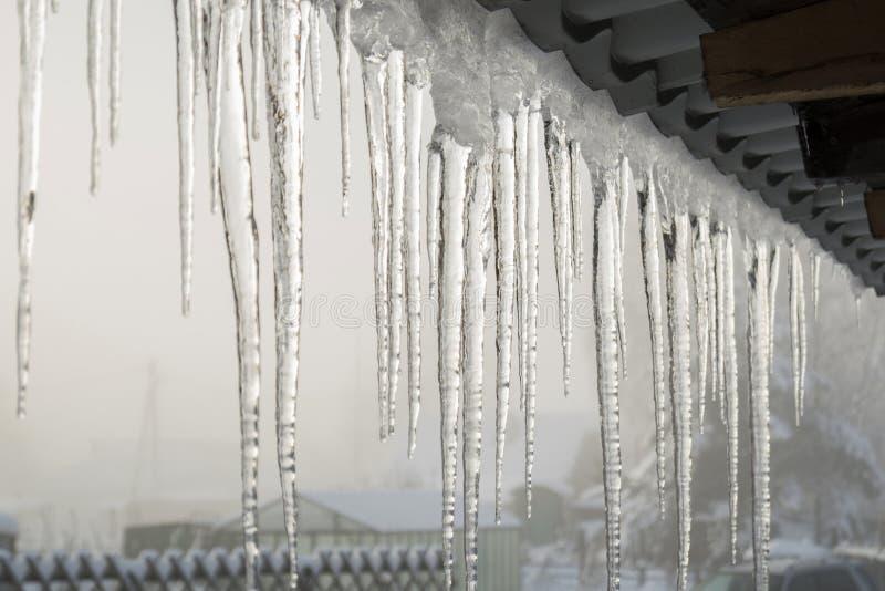 Eiszapfen auf den Dachgesimsen stockfoto