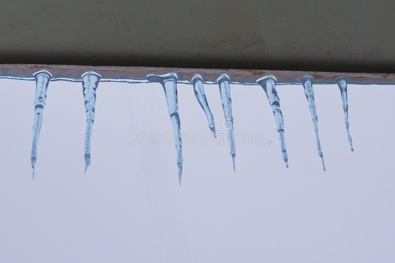 Eiszapfen auf den Dachgesimsen lizenzfreies stockfoto