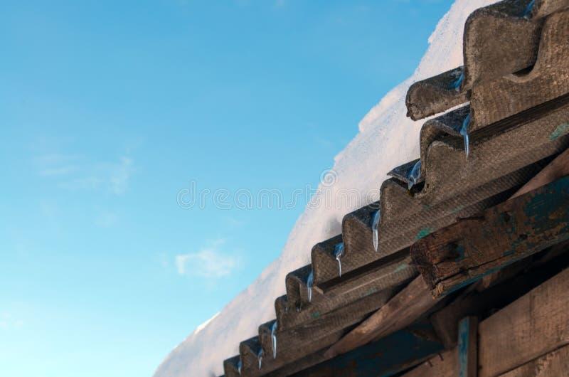 Eiszapfen auf der Dachnahaufnahme Der Anfang des Frühlinges Hintergrund stockfotos