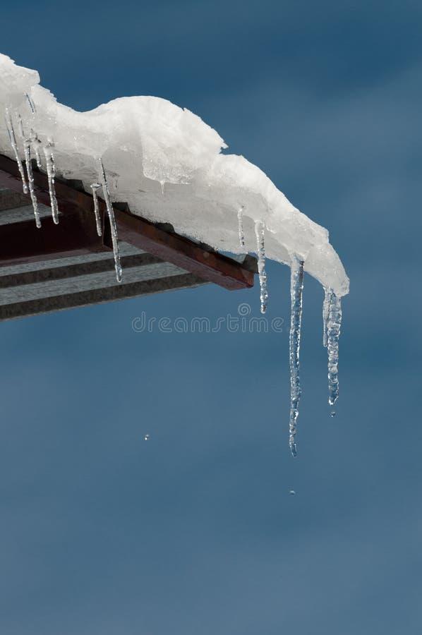 Eiszapfen auf einem Dach auf einem blauen Hintergrund stockfotografie