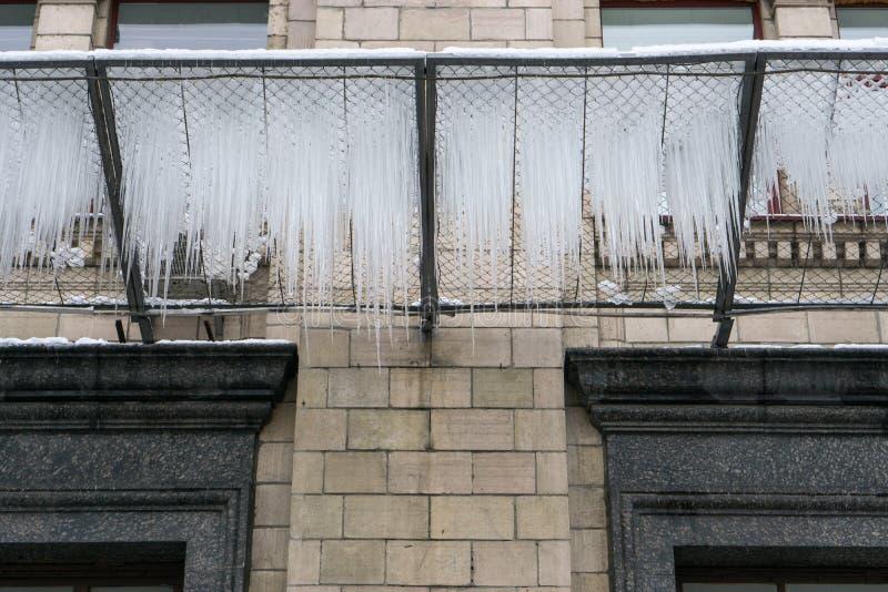 Eiszapfen auf einem Gitter unter dem Gebäude am Winter stockfoto