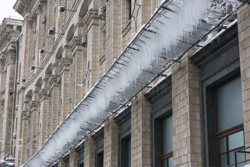 Eiszapfen auf einem Gitter unter dem Gebäude am Winter lizenzfreies stockbild