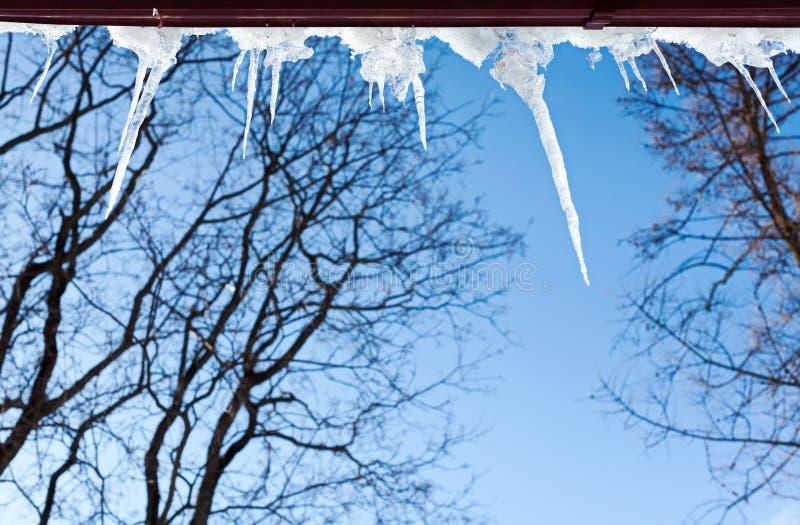 Eiszapfen, die von einem Dach hängen lizenzfreie stockfotografie