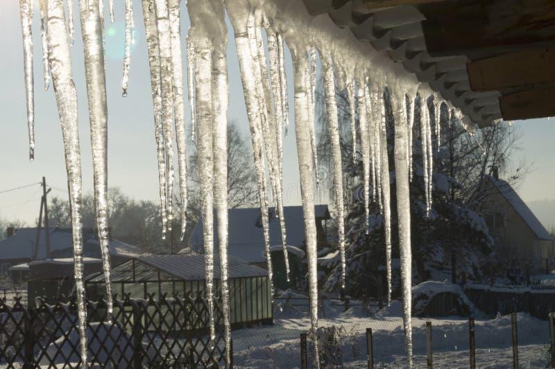 Eiszapfen im Wintertauwetter auf der Leiste stockbilder