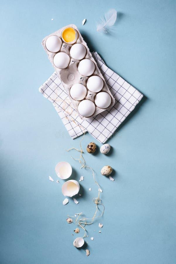 Eiwiteieren of kippeneieren in een pak voor eieren, kwartelseieren, voedselachtergrond Gebarsten ei met wit en dooier over blauw  stock afbeelding