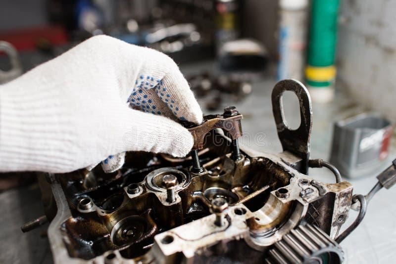 Eixo de manivela do motor, tampa da válvula, pistões Reparador do mecânico no trabalho do reparo da manutenção do motor de automó fotografia de stock