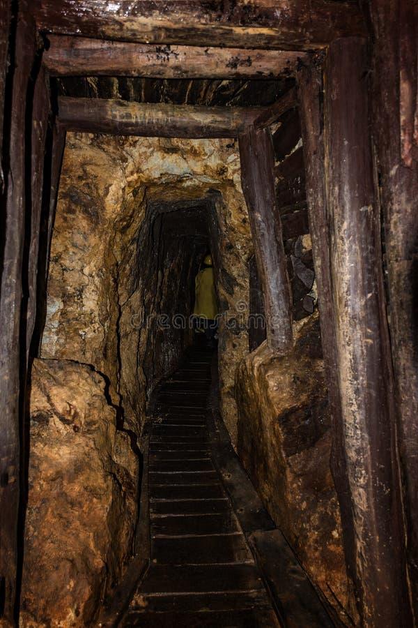 Eixo de mina velho com suportar de madeira e pessoa vestida em uma cornija de lareira de mineração no fundo imagem de stock