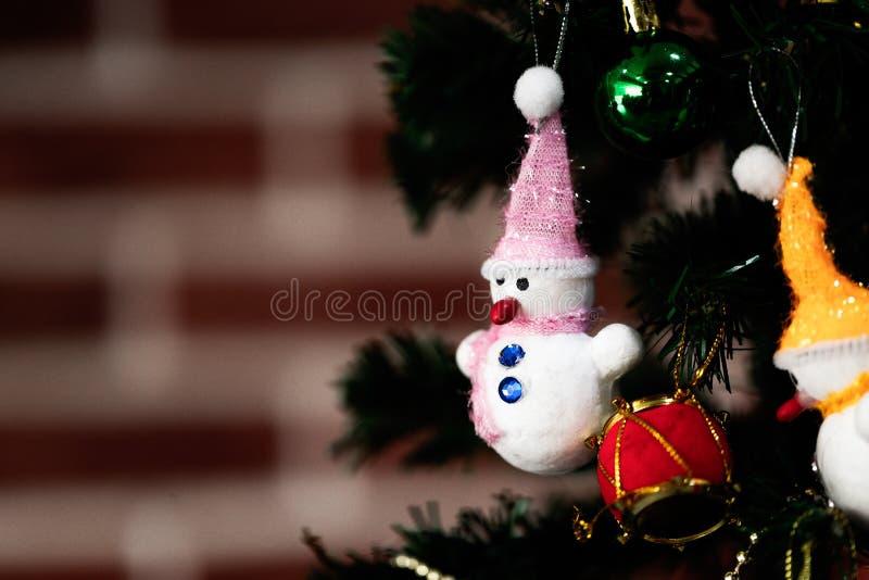 Ejecución blanca de la muñeca del muñeco de nieve en el árbol de pino falso adornado en hogar imagen de archivo