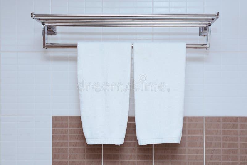 Ejecución blanca de la toalla en la pared del cuarto de baño con la toalla de la ejecución foto de archivo