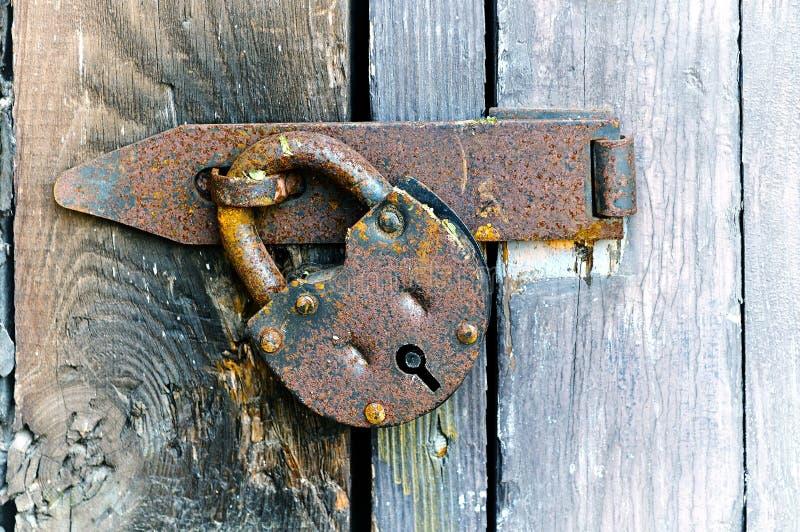 Ejecución de acero oxidada del candado en la puerta resistida de madera foto de archivo libre de regalías