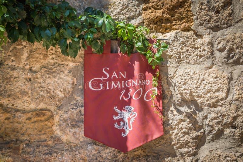 Ejecución de la bandera de la bandera en la pared en San Gimignano, Italia imagen de archivo libre de regalías
