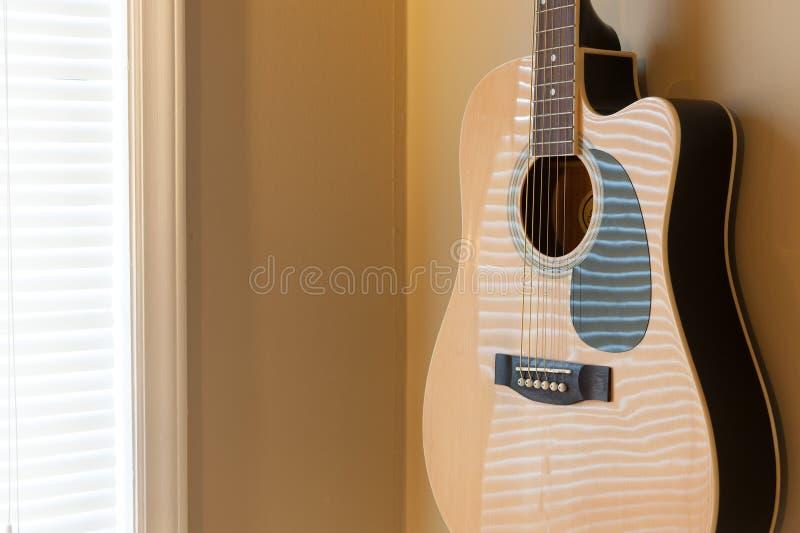 Ejecución de la guitarra acústica en la pared fotografía de archivo