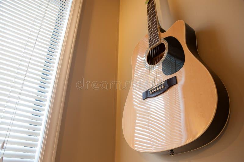 Ejecución de la guitarra acústica en la pared imagen de archivo