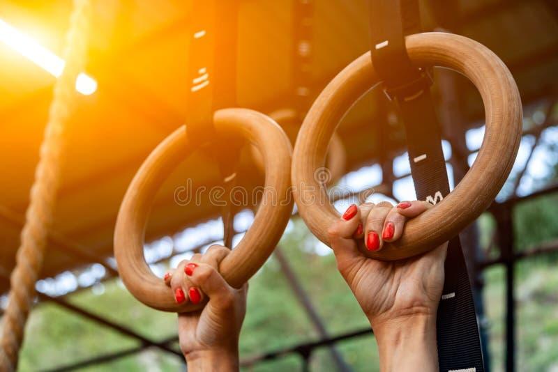 Ejecución de la mujer joven en los anillos del gimnasio imagen de archivo