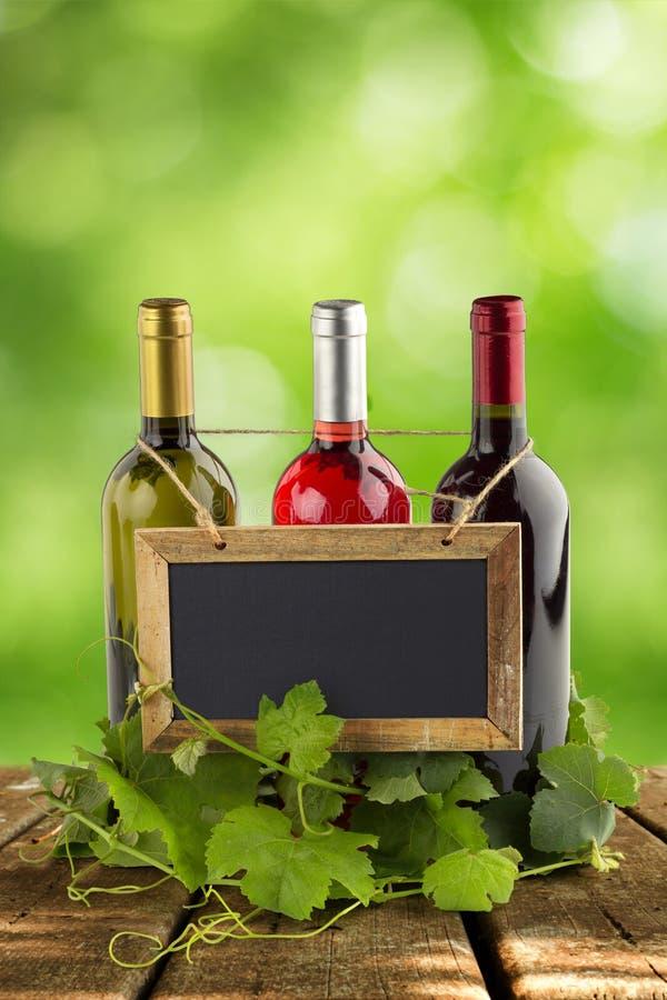 Ejecución de la pizarra en las botellas de vino fotos de archivo libres de regalías