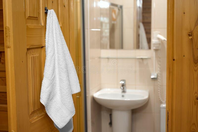 Ejecución de la toalla en la puerta del cuarto de baño fotos de archivo libres de regalías