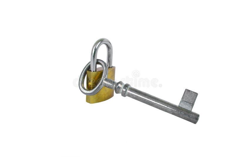 Ejecución de plata de la llave del vintage en la cerradura del oro aislada en el fondo blanco foto de archivo libre de regalías