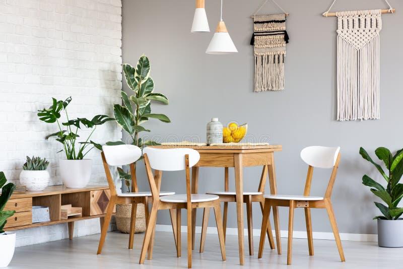 Ejecución del agremán en la pared gris sobre la tabla de madera y sillas en Br fotografía de archivo libre de regalías