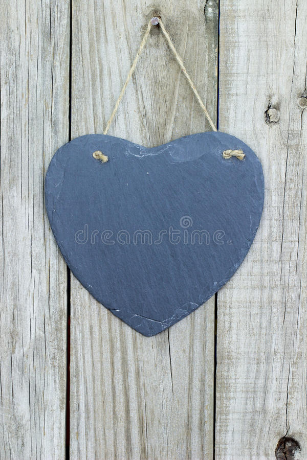 Ejecución del corazón de la pizarra en puerta de madera rústica imagen de archivo