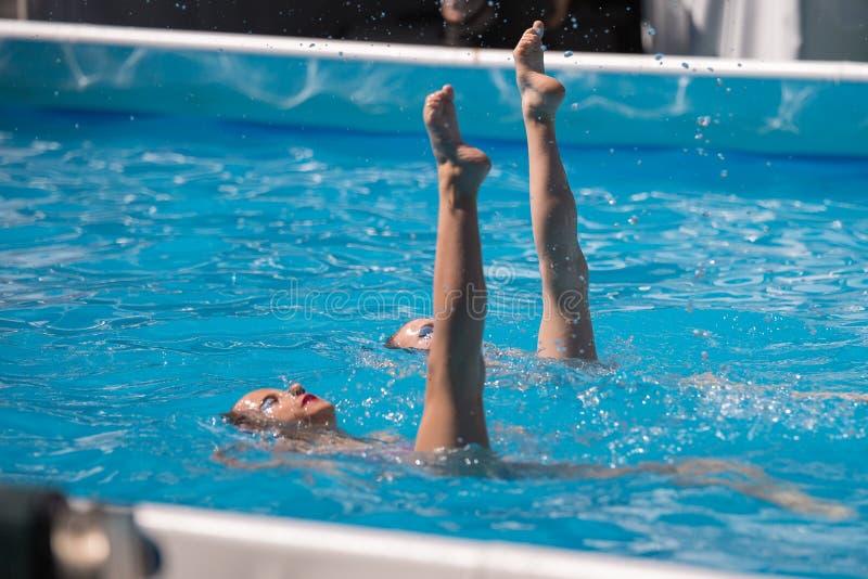 Ejecución del dúo artístico en piscina: Natación sincronizada durante ejercicio imagen de archivo libre de regalías