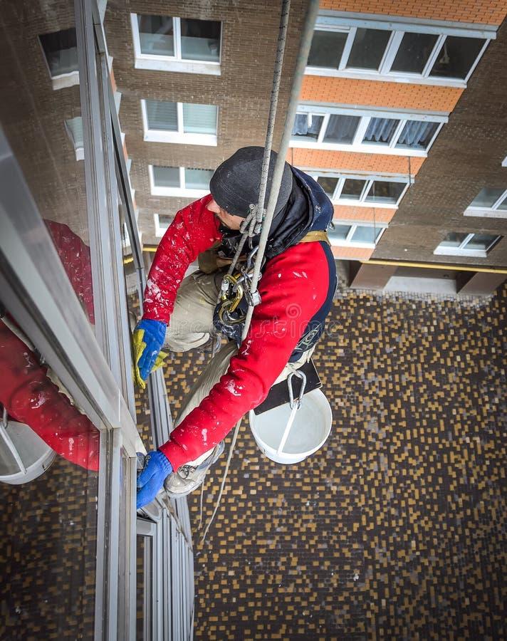 Ejecución del limpiador de ventana en cuerda imagenes de archivo