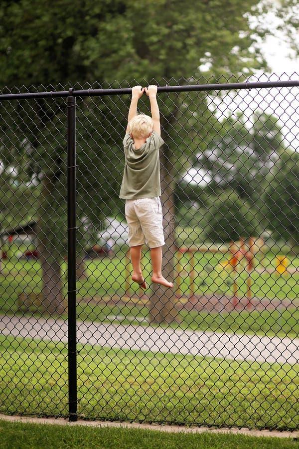 Ejecución del niño de Little Boy de la alta cerca Trying de la alambrada al Cl fotos de archivo libres de regalías