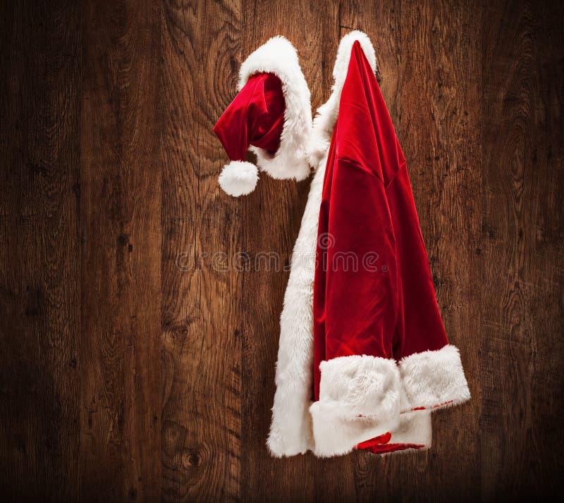 Ejecución del traje de Papá Noel en una pared de madera fotografía de archivo