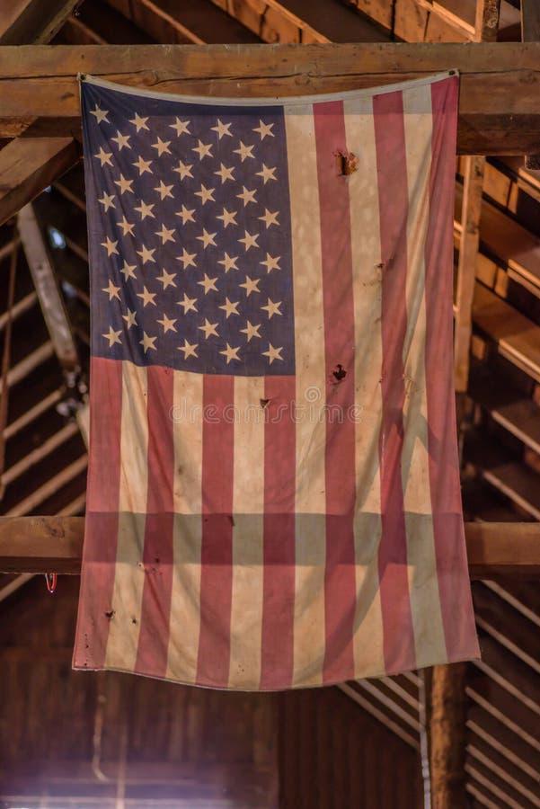 Ejecución hecha andrajos y descolorada de la bandera americana en granero viejo fotos de archivo libres de regalías