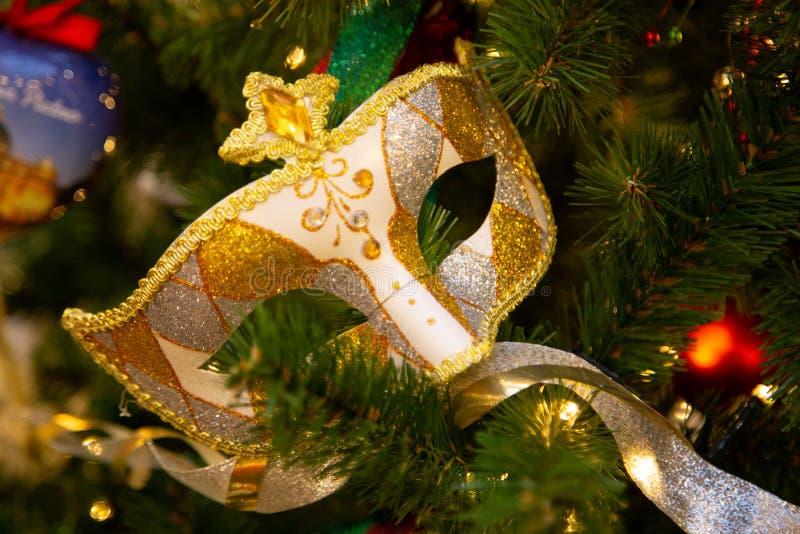 Ejecución hermosa de la máscara del carnaval en el árbol de navidad en el fondo de las decoraciones brillantes de Christmass fotografía de archivo